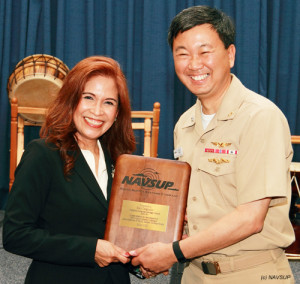 Rear Admiral Jonathan A. Yuen, commanding officer of U.S. Navy Supply Corps H.Q. in Mechanicsburg, PA, presents Emy Delgaudio with plaque after her remarks to his Assembly.