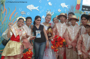 Philippine American Heritage Council Chairman Emy Delgaudio with the Queen of one of the participating groups, holding the image of the Santo Nino – and with her Dance Troupe who participated in the festive and massive parade of Sinulog in Cebu City, Philippines, 2005.